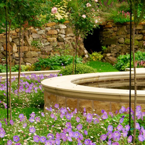 Formal raised water feature, clipped holly balls and Geranium Jolly Bee, designed by Carolyn Grohmann