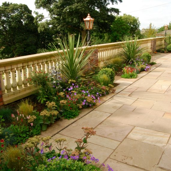 Terrace overlooking garden with herbaceous planting, clipped holly and Cordyline, designed by Carolyn Grohmann