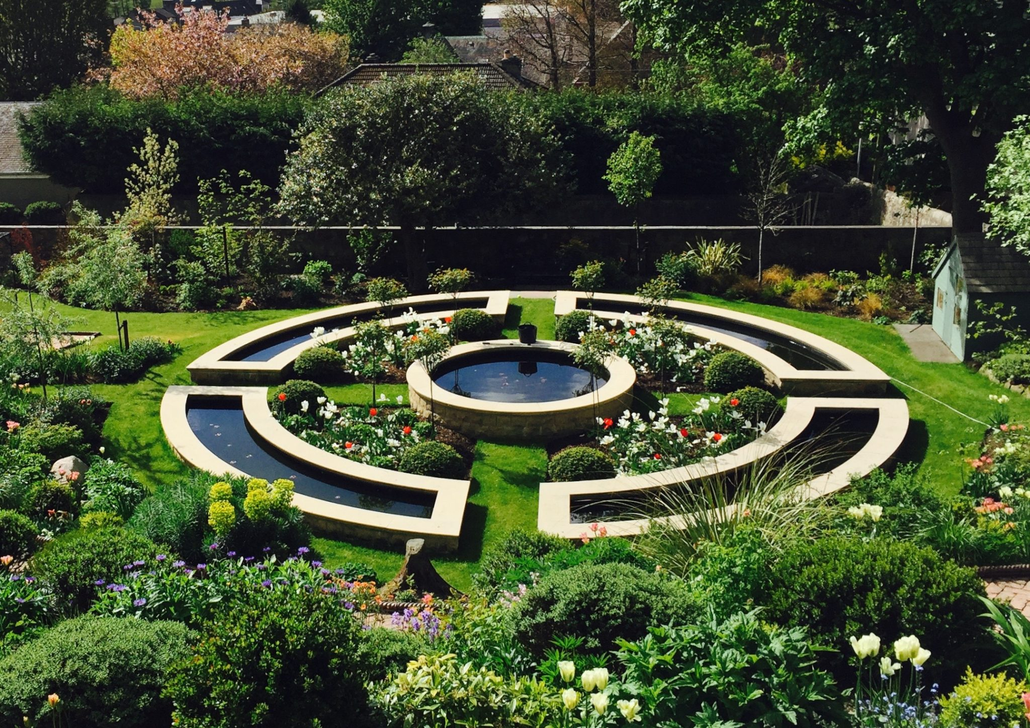 Formal water feature with tulips in full bloom. Designed by Carolyn Grohmann