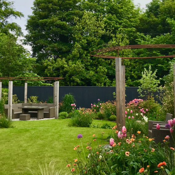 Larch and rebar pergolas, circular lawns and lush herbaceous planting designed by Carolyn Grohmann