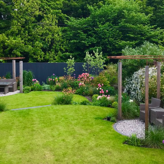 Larch and rebar pergolas, circular lawns and lush herbaceous planting