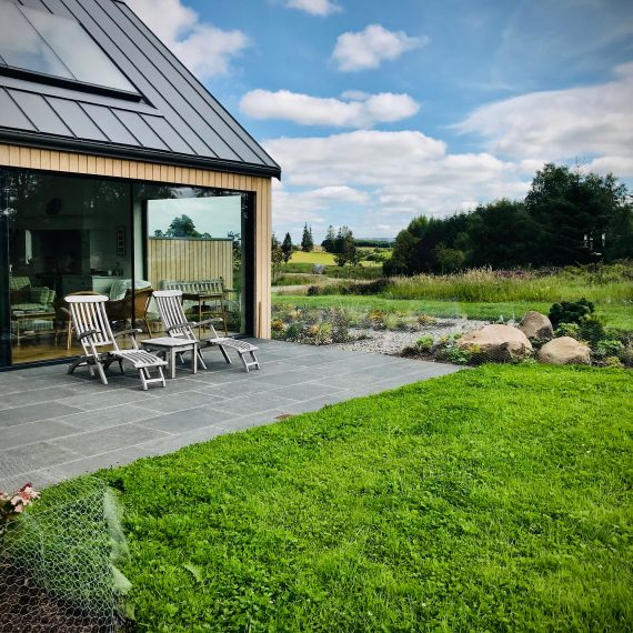 South-west facing patio with recently planted borders and species rich turf. Designed by Carolyn Grohmann