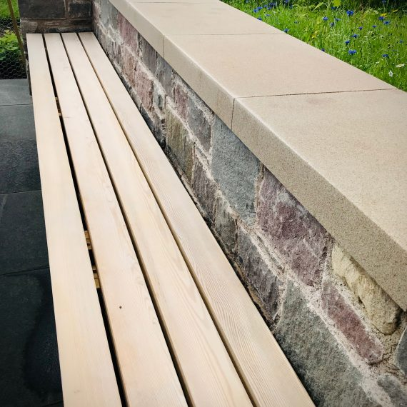 Walling to match house walls, Siberian larch bench to match house cladding. Designed by Carolyn Grohmann