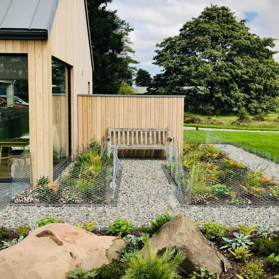 Timber wall creating shelter from the wind with seating on both sides. Designed by Carolyn Grohmann