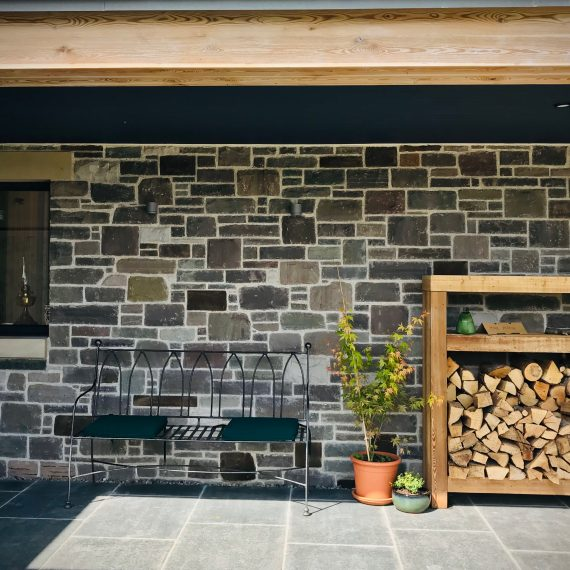 Covered front door area with bench, log store. Designed by Carolyn Grohmann