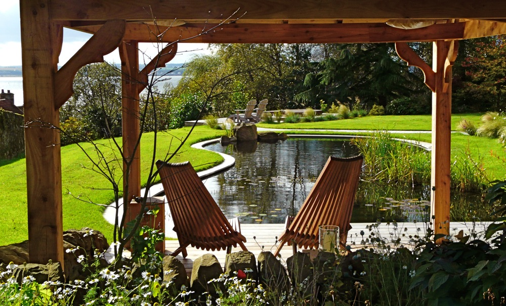 View through the arbour across the pond. Garden designed by Carolyn Grohmann