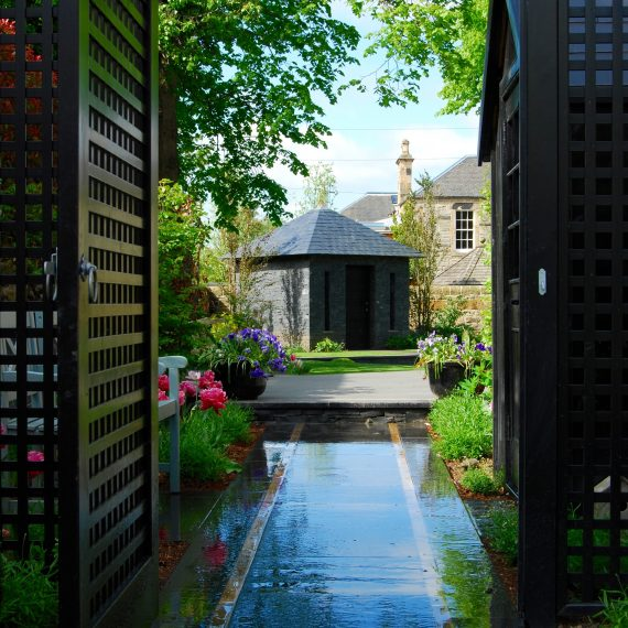 View through side garden to stone and slate garden building, designed by Carolyn Grohmann