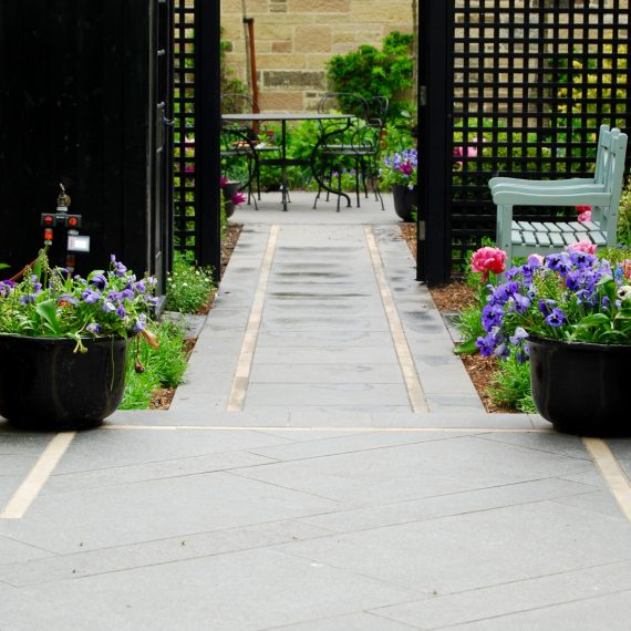 Side garden view through black square trellis, black basalt path with Clashach inlay, designed by Carolyn Grohmann
