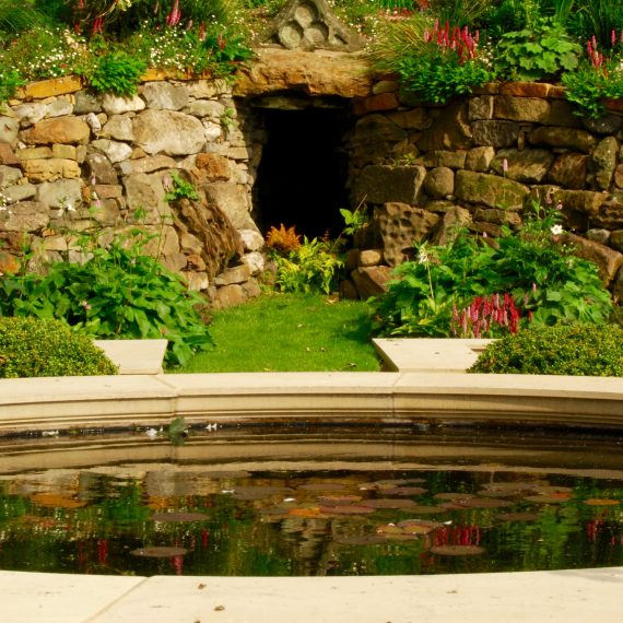 Formal raised water feature with grotto in background, garden designed by Carolyn Grohmann