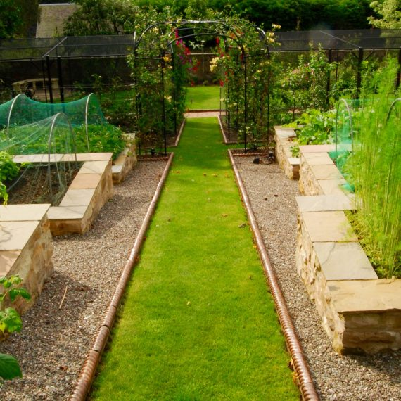 Lawn paths and raised vegetable beds, roses arbours, designed by Carolyn Grohmann