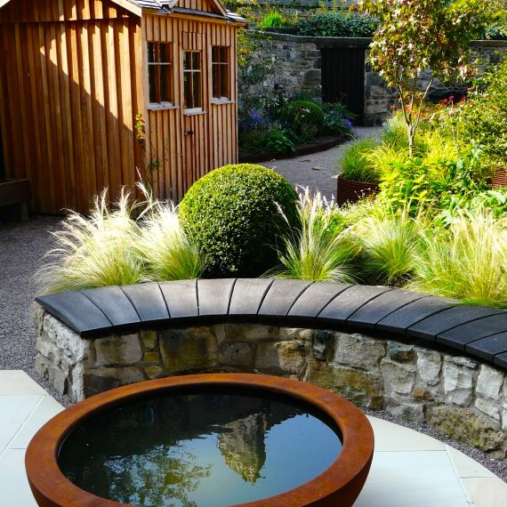 Urbis lily bowl, scorched oak bench, garden designed by Carolyn Grohmann