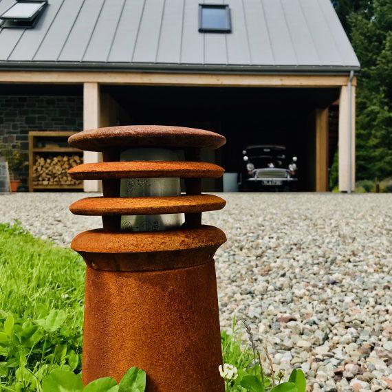 Rusty bollard light at edge of driveway with species rich turf. Designed by Carolyn Grohmann