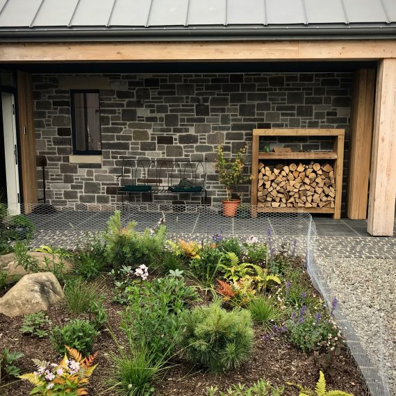 Front door area: bench, logstore, planting. Designed by Carolyn Grohmann